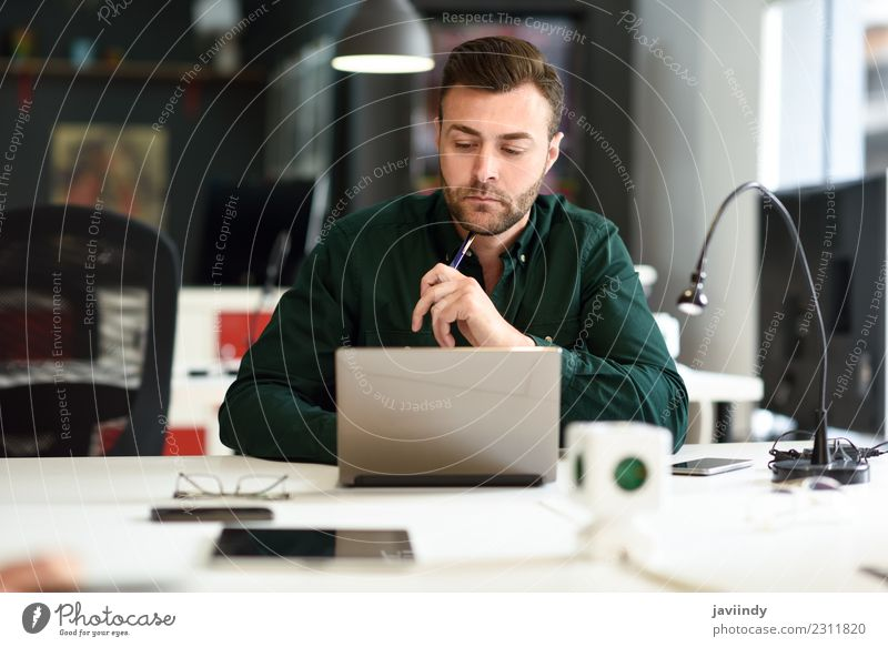 Young man studying with laptop computer on white desk. Lifestyle Happy School Study Academic studies Work and employment Business Computer Notebook Technology