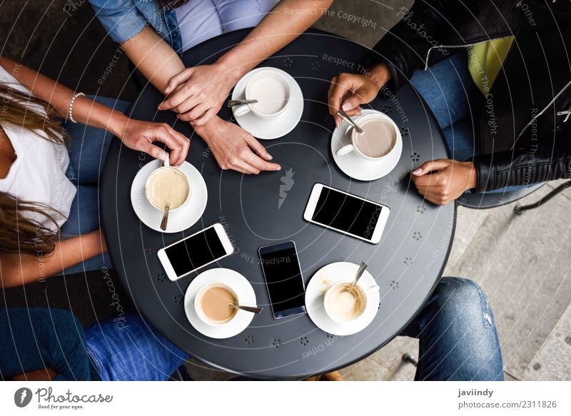 Coffee cups and smartphones on table in a urban cafe. Breakfast Beverage Lifestyle Shopping Table Meeting To talk Telephone PDA Human being Young woman