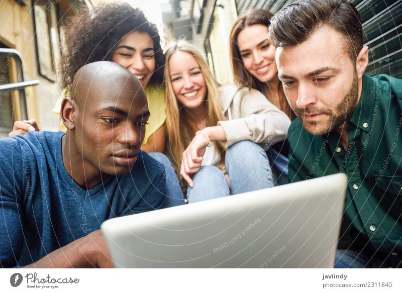 Multi-ethnic group of young people looking at a tablet computer outdoors Lifestyle Joy Happy Beautiful Young woman Youth (Young adults) Young man Woman Adults