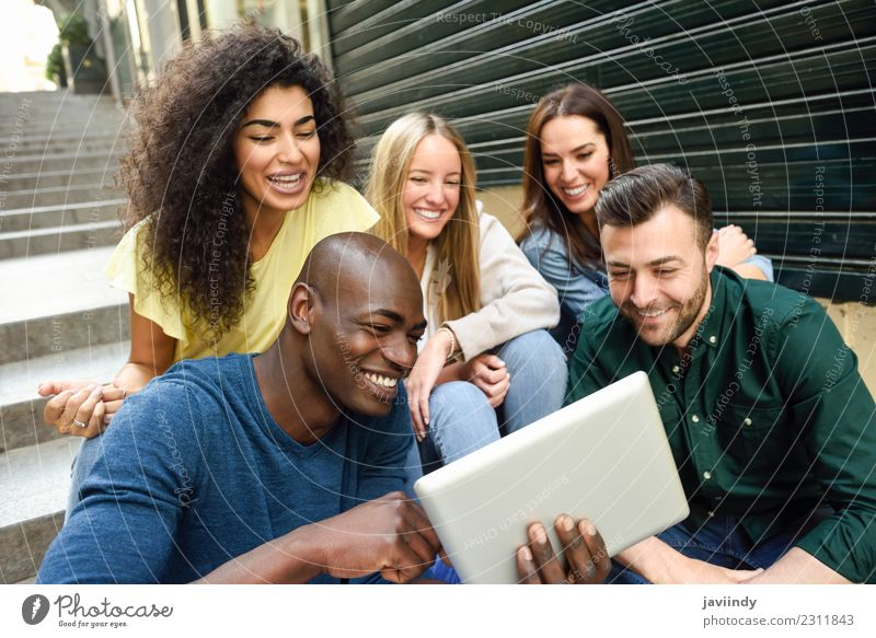 Multi-ethnic young people looking at a tablet computer Lifestyle Joy Happy Beautiful Human being Young woman Youth (Young adults) Young man Woman Adults Man