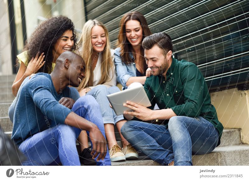 Multi-ethnic group of people looking at a tablet computer Woman Human being Youth (Young adults) Man Young woman Beautiful Young man Joy 18 - 30 years Adults