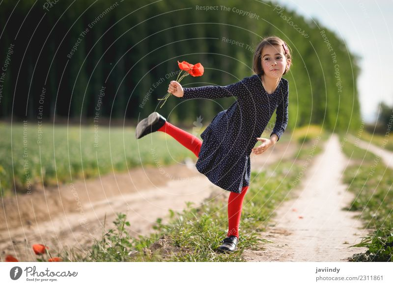 Funny little girl in nature with poppies in her hand. Child Woman Human being Nature Summer Beautiful Flower Joy Girl Adults Lifestyle Meadow Grass Small Happy
