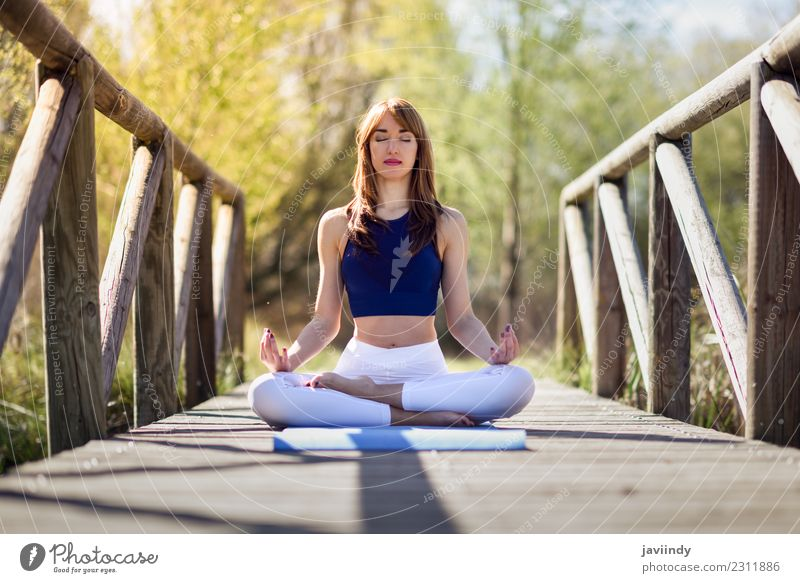Woman doing yoga in nature. Lotus figure on wooden bridge. Lifestyle Body Relaxation Meditation Sports Yoga Human being Young woman Youth (Young adults) Adults
