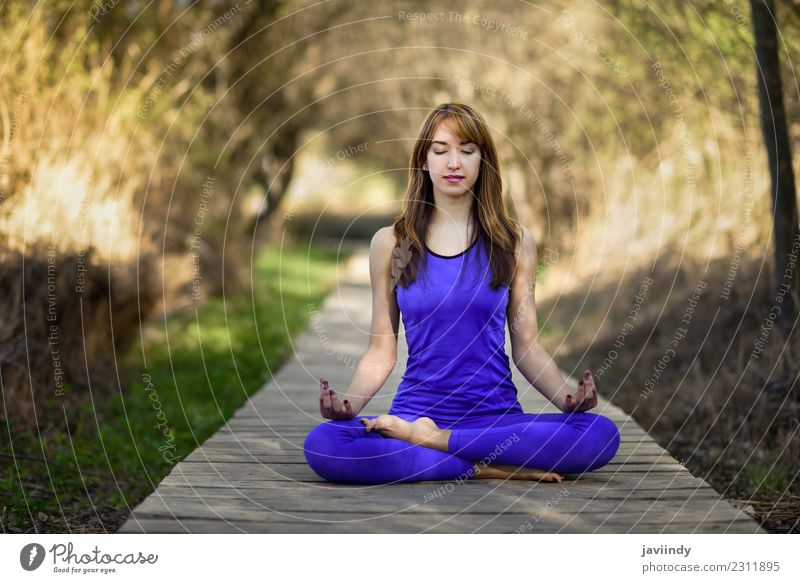 Young woman doing yoga in nature. Lotus figure. Lifestyle Beautiful Body Relaxation Meditation Summer Sports Yoga Human being Youth (Young adults) Woman Adults