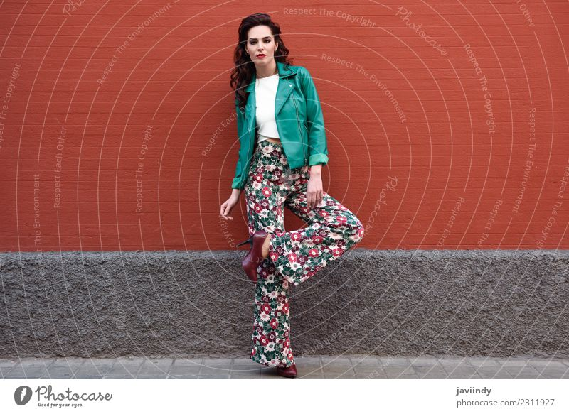 Young brunette woman, model of fashion, wearing green modern jacket and flower pants on red wall Lifestyle Style Beautiful Hair and hairstyles Face Human being