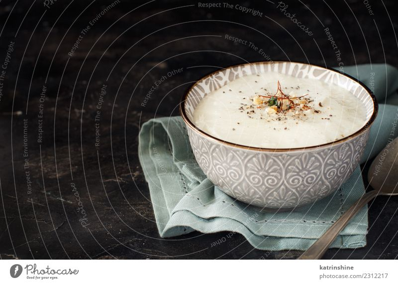 Creamy cauliflower soup in a bowl on a dark background Vegetable Soup Stew Herbs and spices Lunch Dinner Vegetarian diet Diet Bowl Spoon Table Child Gastronomy