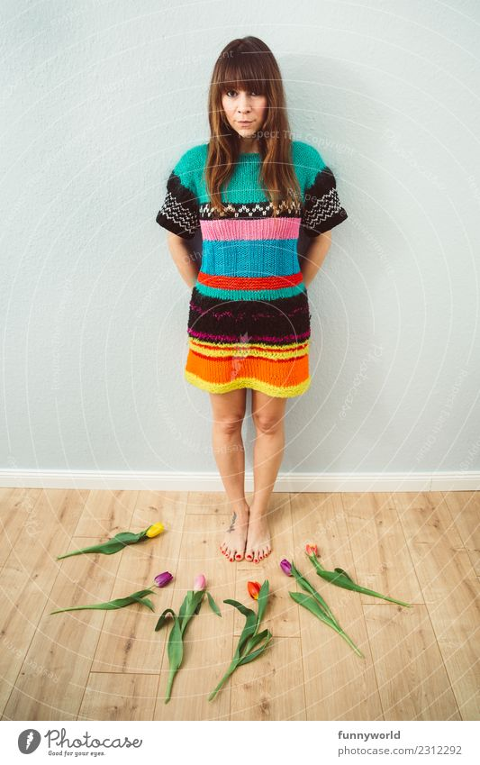 Woman in a wool dress surrounded by tulips Human being Feminine Adults 1 Brunette Bangs Looking Stand Funny Natural Center point Arrangement Whimsical Joy Tulip