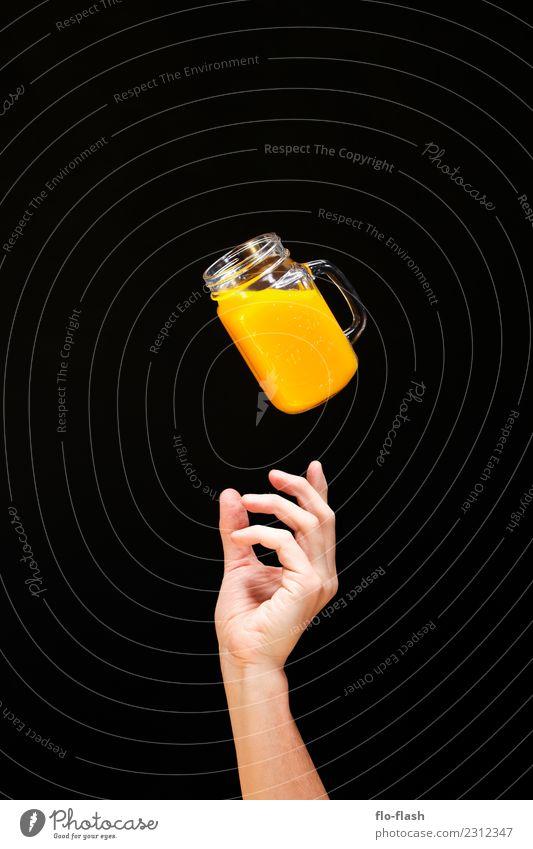 ONE HAND REACHES FROM BELOW FOR A GLASS OF YELLOW FLUID Food Fruit Orange Breakfast Organic produce Vegetarian diet Diet Fasting Beverage Lemonade Juice