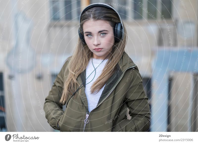 Young girl with headphones standing on the street Lifestyle Joy Happy Beautiful Relaxation Leisure and hobbies Music Technology Human being Woman Adults