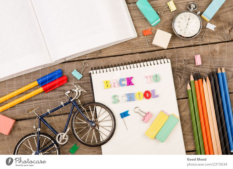 "inscription of ""back to school"", bicycle model, stopwatch, book Child Wood School Bright Office Infancy Vantage point Table Book Paper Academic studies Model"