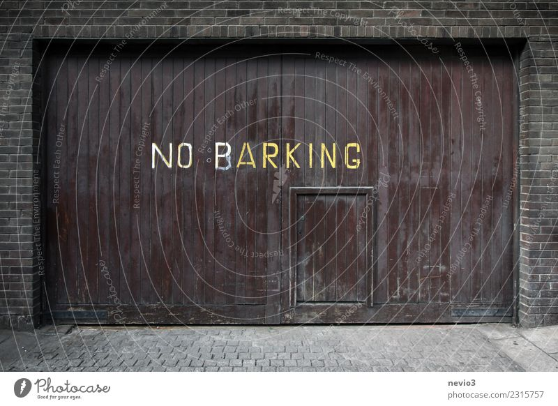 Note on a garage door Town Capital city Downtown House (Residential Structure) Places Parking garage Street Road sign Brown Garage door Parking lot