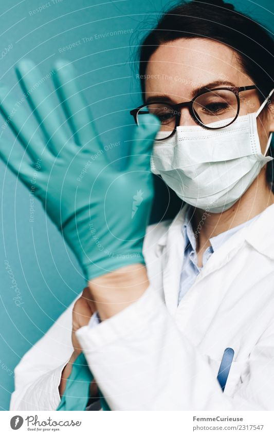 Female doctor putting on protective gloves Work and employment Profession Doctor Feminine Young woman Youth (Young adults) Woman Adults 1 Human being
