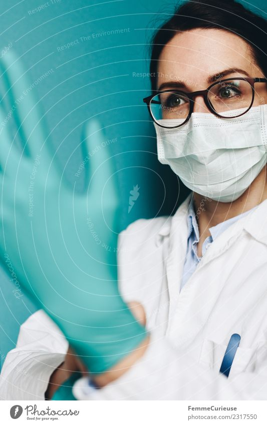 Female doctor putting on her protective gloves Work and employment Profession Doctor Feminine Young woman Youth (Young adults) Woman Adults 1 Human being