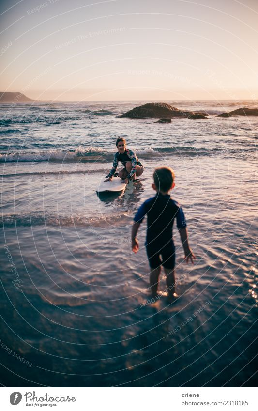 Mother teaching her son surfing with surfboard Lifestyle Joy Happy Relaxation Leisure and hobbies Vacation & Travel Summer Beach Ocean Sports Child Boy (child)