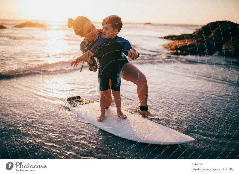 Little boy and mother practicing surfing at beach Child Vacation & Travel Summer Ocean Relaxation Joy Beach Adults Lifestyle Sports Family & Relations
