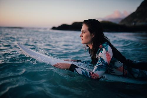 Young female adult laying on surfboard in the water Lifestyle Joy Happy Beautiful Leisure and hobbies Vacation & Travel Summer Sun Beach Ocean Waves Sports