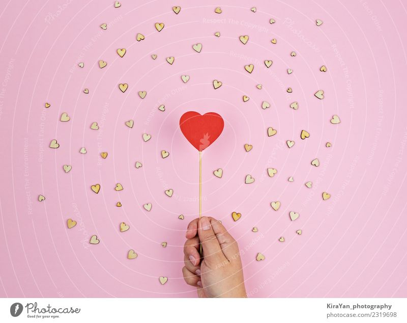 Hand holds large red wooden heart on pink background Red Lifestyle Background picture Love Wood Health care Small Feasts & Celebrations Pink Above