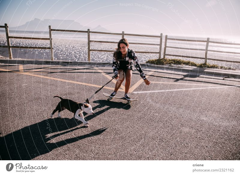 Happy young adult hipster girl on skateboard with puppy Joy Playing Summer Beach Woman Adults Family & Relations Friendship Group Animal Pet Dog Love Embrace