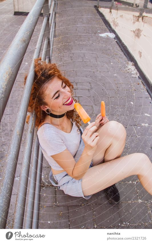 Young woman eating orange ice creams Human being Vacation & Travel Youth (Young adults) Summer Town Joy 18 - 30 years Adults Street Eating Life Lifestyle Funny