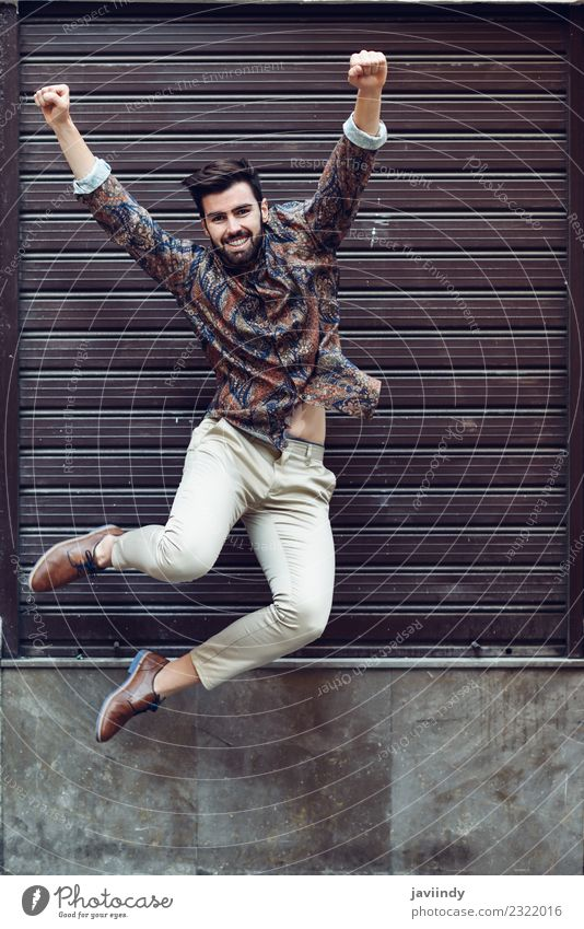 Young bearded man jumping in urban background Joy Human being Masculine Young man Youth (Young adults) Man Adults 1 18 - 30 years Street Fashion Shirt Beard