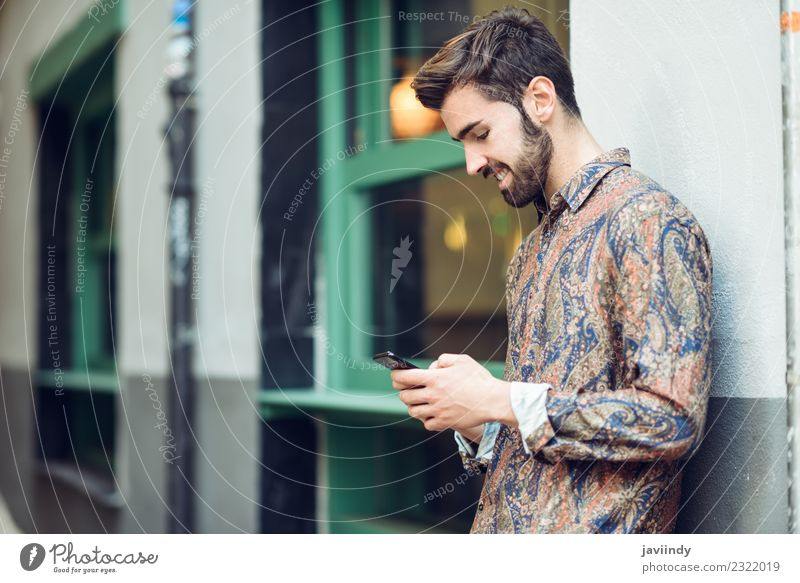 Young smiling man looking at his smartphone in the street Human being Youth (Young adults) Man Beautiful Young man White 18 - 30 years Adults Lifestyle Style