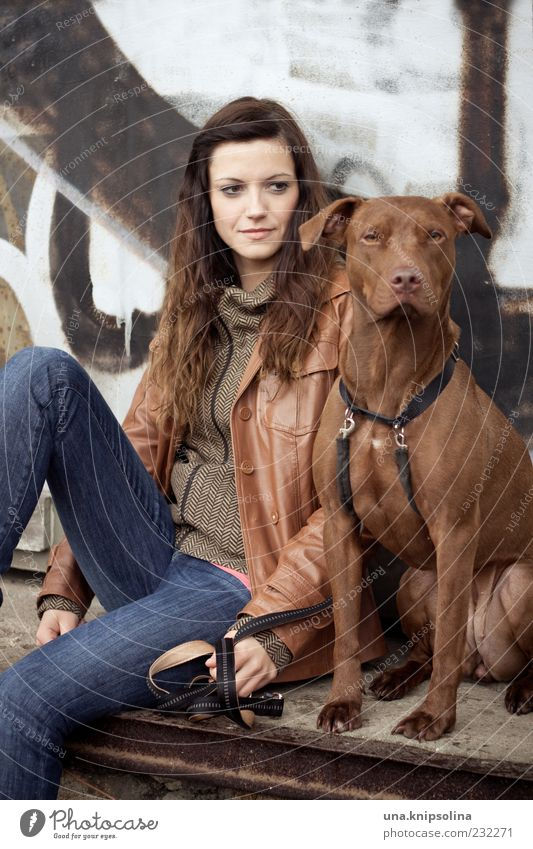 Woman with dog Young woman Youth (Young adults) Adults 1 Human being 18 - 30 years Jeans Jacket Brunette Long-haired Animal Pet Dog Observe To hold on Sit Wait