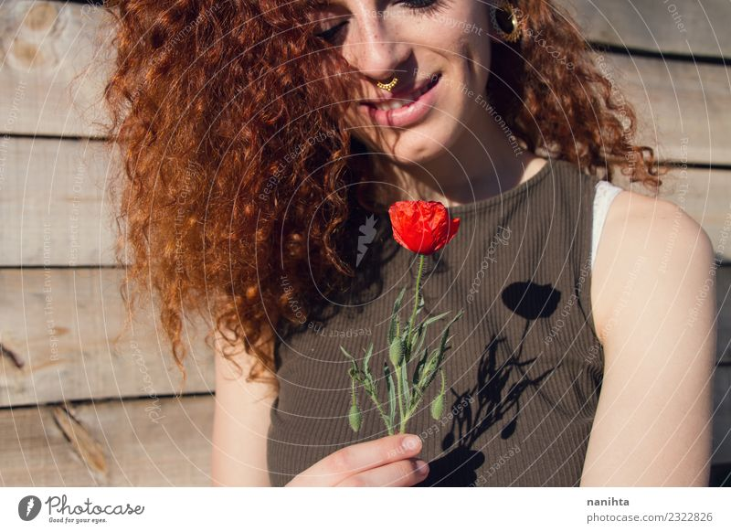Young redhead woman holding a poppy in her hands Lifestyle Style Joy Beautiful Hair and hairstyles Skin Face Wellness Harmonious Senses Relaxation Human being