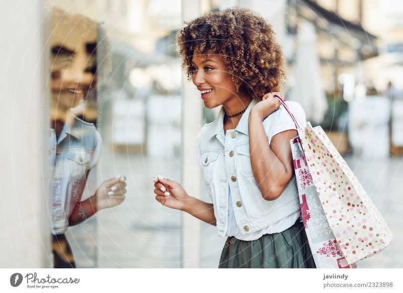 Black woman in front of a shop window in a shopping street Woman Human being Youth (Young adults) Young woman Joy 18 - 30 years Adults Street Lifestyle Feminine