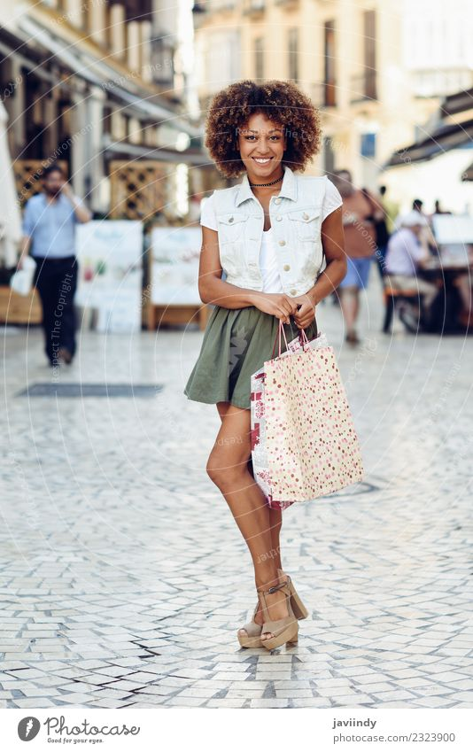 Black woman, afro hairstyle, with shopping bags in the street Woman Human being Youth (Young adults) Young woman Joy 18 - 30 years Adults Street Lifestyle