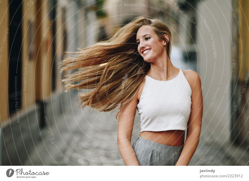 Happy young woman with moving hair in the street Woman Human being Youth (Young adults) Young woman Summer Beautiful White Joy 18 - 30 years Adults Street