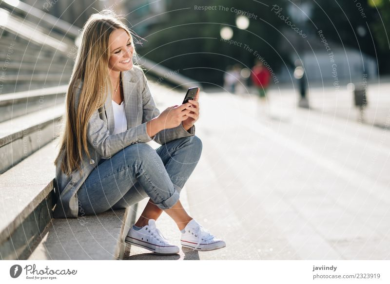 Woman looking at her smartphone and smiling in urban background Lifestyle Style Happy Beautiful Hair and hairstyles Telephone PDA Human being Feminine
