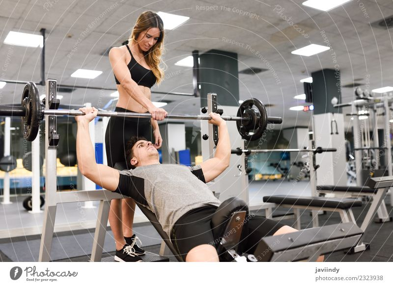 Female personal trainer helping a young man lift weights Lifestyle Body Sports Human being Young woman Youth (Young adults) Young man Woman Adults Man 2