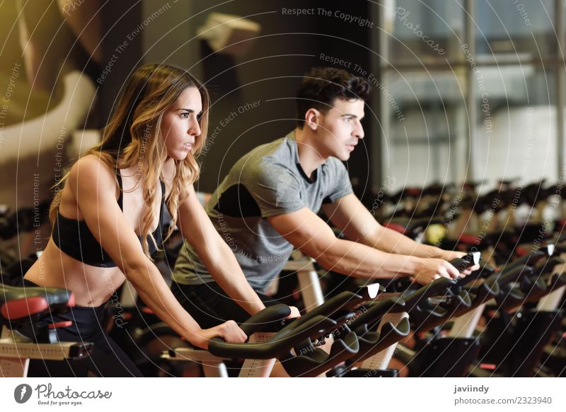 Two people biking in the gym, indoor cycling bikes. Lifestyle Leisure and hobbies Sports Work and employment Human being Young woman Youth (Young adults)