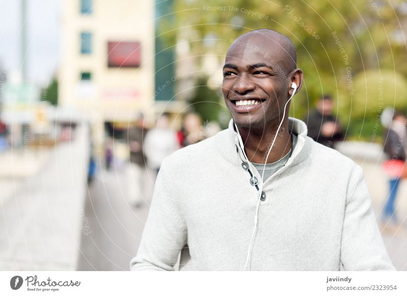 Smiling black man with earphones in the street Lifestyle Happy Beautiful Face Human being Masculine Young man Youth (Young adults) Man Adults 1 18 - 30 years