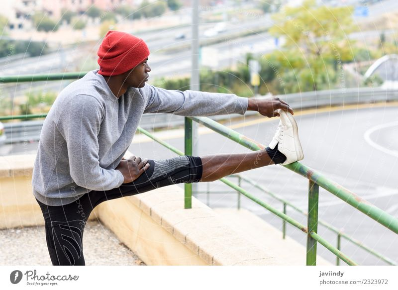 Black man doing stretching after running outdoors Lifestyle Body Winter Sports Jogging Human being Masculine Young man Youth (Young adults) Man Adults 1