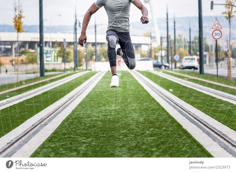Black man jumping in urban background. Lifestyle Sports Jogging Human being Masculine Young man Youth (Young adults) Man Adults 1 18 - 30 years Street Fitness