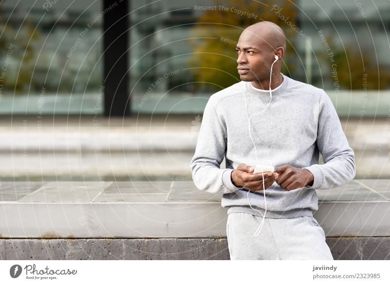 Attractive black man listening to music with headphones outdoors Lifestyle Happy Music Sports Telephone PDA Technology Human being Young man