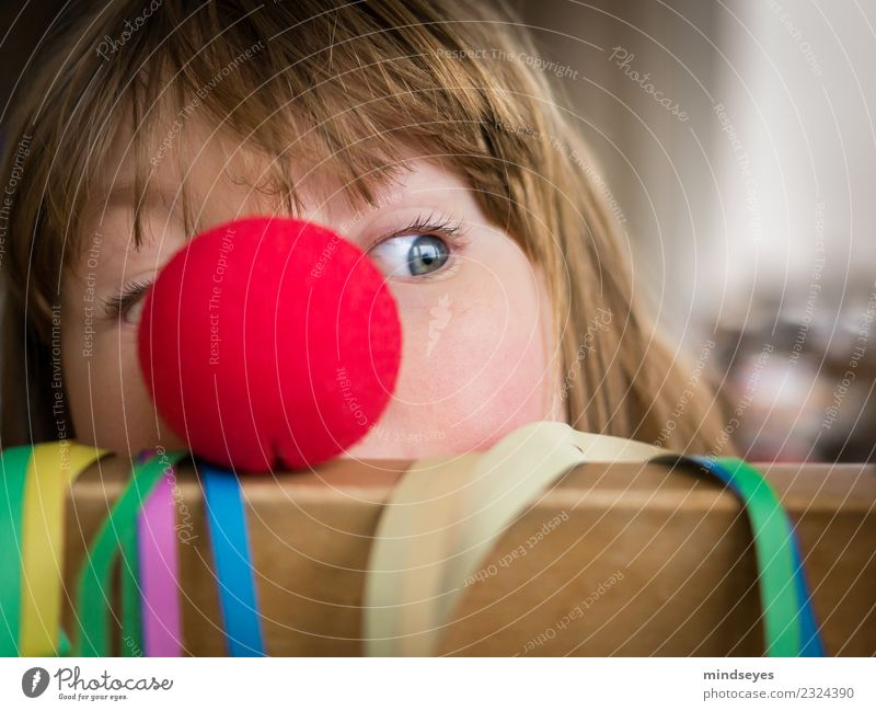 Blonde girl peeping out from behind a red clown nose. Joy Playing Carnival Infancy 1 Human being 3 - 8 years Child Circus Party Paper streamers Nose