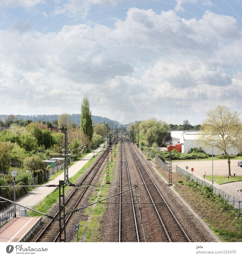 shuttle Sky Clouds Plant Tree Grass Bushes Manmade structures Building Rail transport Railroad tracks Railroad system Colour photo Exterior shot Deserted