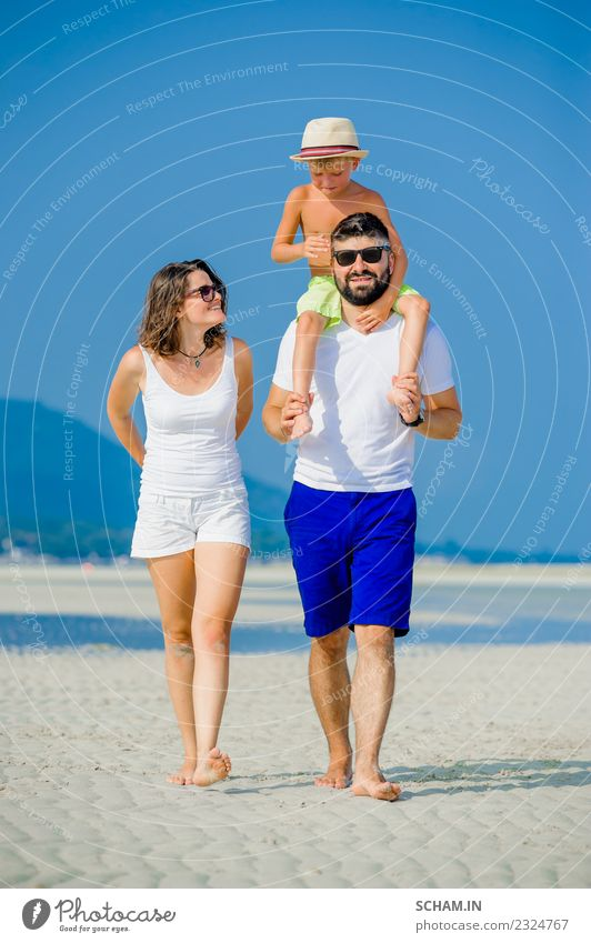 Happy young family of three at the beach Lifestyle Joy Playing Summer Ocean Island Infancy Group Sunglasses Beard Smiling Happiness Together 30-34 years