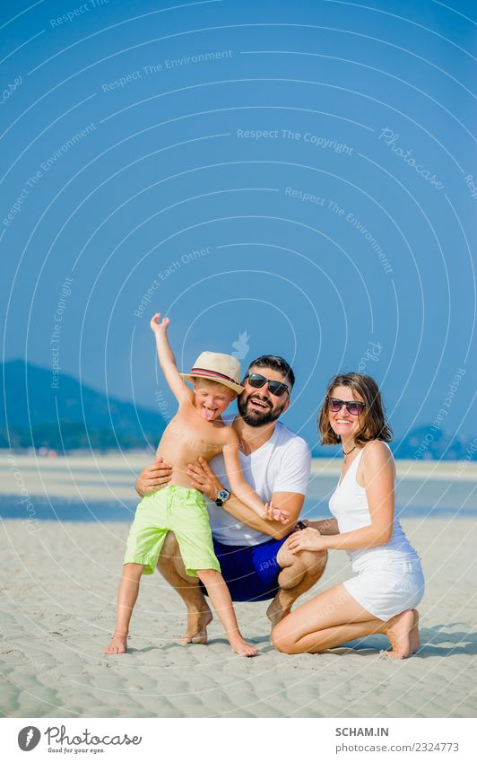 Happy young family of three having fun on the desert sunny beach Child Woman Human being Man Summer Ocean Joy Adults Lifestyle Natural Feminine Laughter