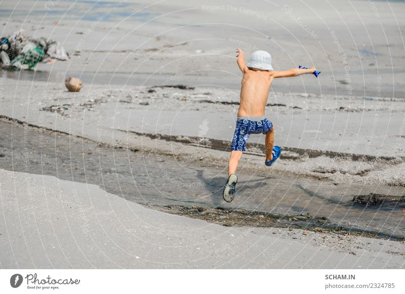 Seven years old boy jumping over the small river Lifestyle Joy Playing Summer Ocean Island Human being Child Boy (child) Infancy 1 3 - 8 years Landscape Hat