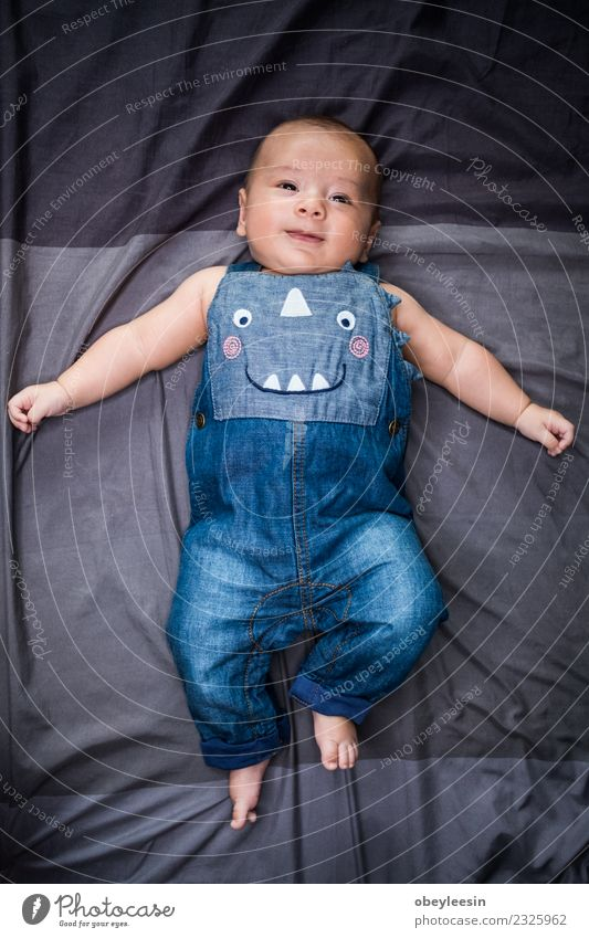 cute baby lying in a bead wearing jean dungarees Happy Beautiful Face Bathroom Child Human being Baby Toddler Boy (child) Woman Adults Infancy Toys Smiling