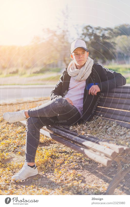 Stylish teenager sitting on a wooden bench Lifestyle Happy Calm Schoolchild Academic studies PDA Human being Boy (child) Man Adults Youth (Young adults) Autumn