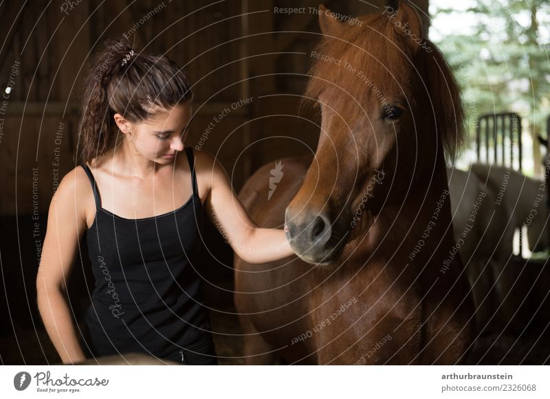 Young dark-haired curly woman with horse in stable Leisure and hobbies Ride Equestrian sports Riding school Vacation & Travel Trip Riding stable Riding hall