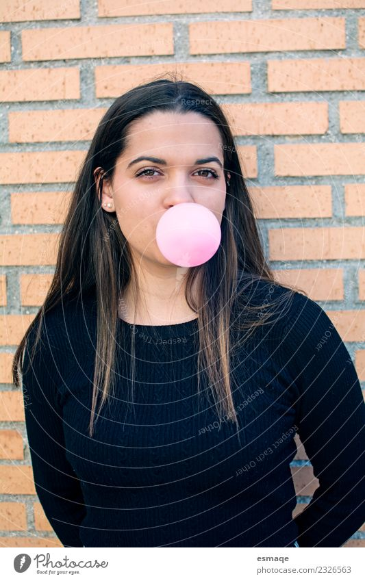 portrait of young woman eating bubble gum in brick background Vacation & Travel Youth (Young adults) Young woman Colour Joy Girl Lifestyle Wall (building)
