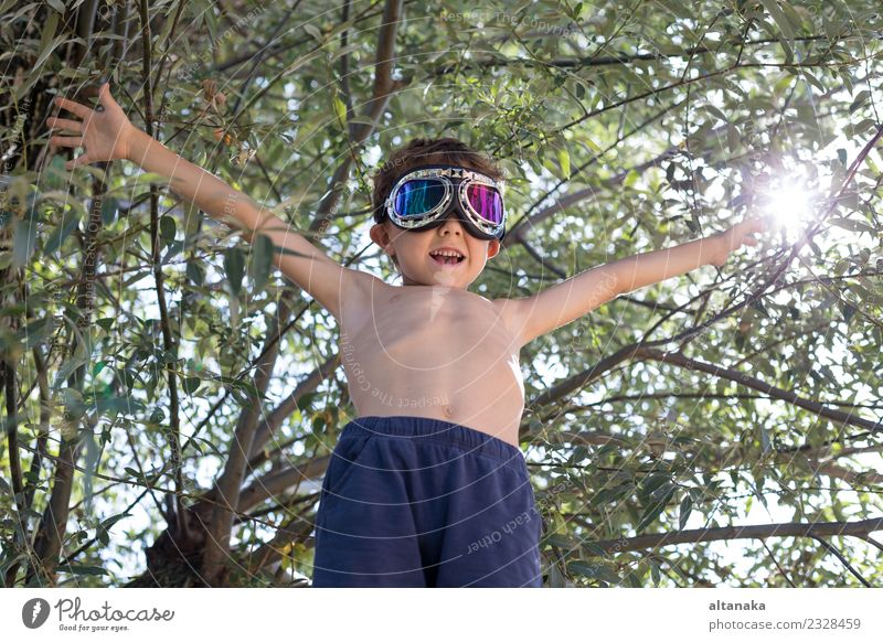 Happy little boy playing outdoors near a tree Lifestyle Joy Playing Vacation & Travel Trip Adventure Freedom Summer Success Child Pilot Human being Boy (child)