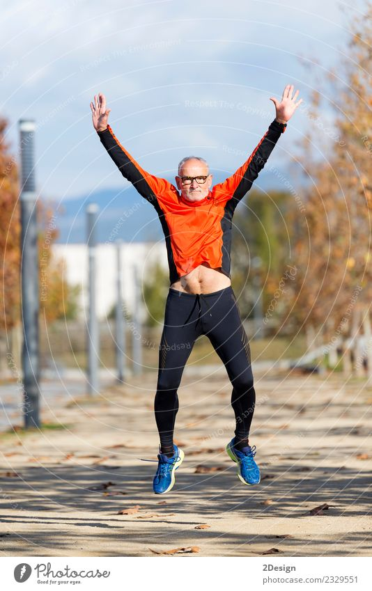 Senior runner man jumping arms up after running Lifestyle Joy Happy Body Healthy Leisure and hobbies Sports Track and Field Sportsperson Success Jogging