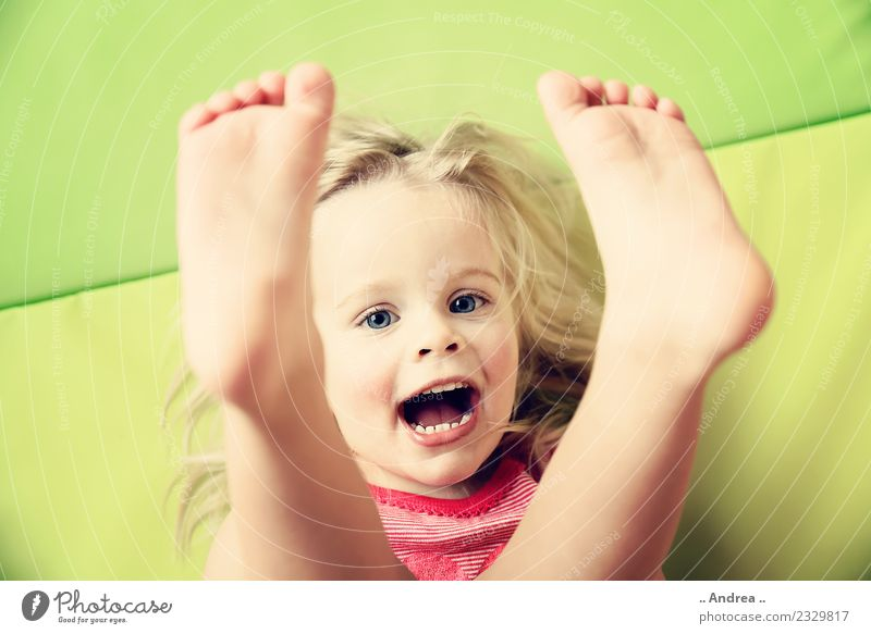Feet up ... Child Toddler Girl Face 1 Human being 1 - 3 years Movement Fitness Smiling Laughter Lie Playing Sports Happiness Fresh Healthy Happy Beautiful Cute