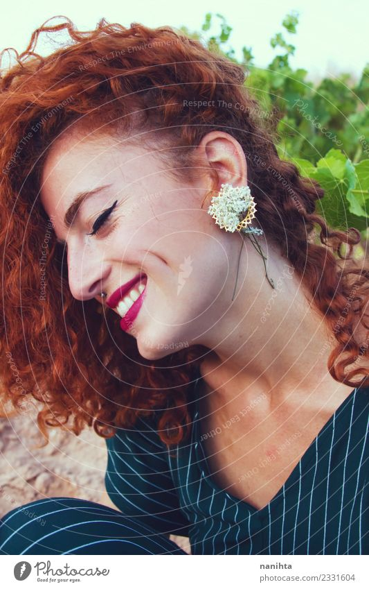 Young redhead woman with flowers as earring Human being Nature Youth (Young adults) Young woman Beautiful Flower Joy 18 - 30 years Face Adults Lifestyle